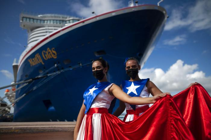 Ivanelis Jimenez, front, and Veronica Barreto pose for the camera wearing Puerto Rican flag dresses as they welcome passengers exiting Carnival's Mardi Gras cruise ship.